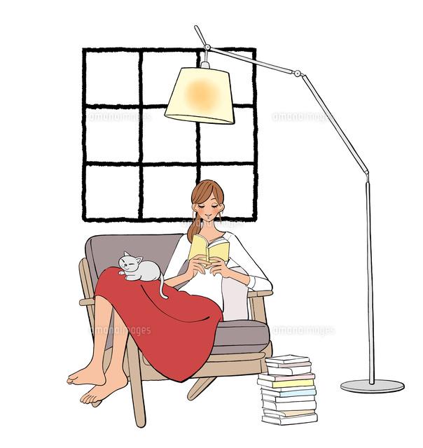 ソファに座り本を読む女の子と膝の上で眠る猫10402000448の写真素材