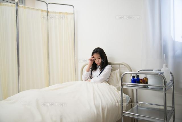 保健室のベッドにいる具合の悪そうな小学生の女の子10568003156の写真