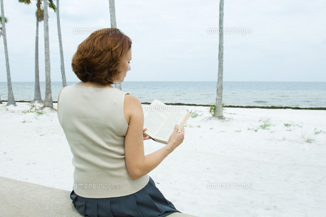 Woman sitting at the beach reading book