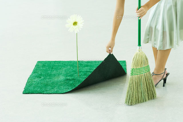 Woman sweeping under artificial turf rug