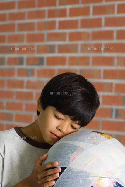 Boy leaning face against bandaged globe