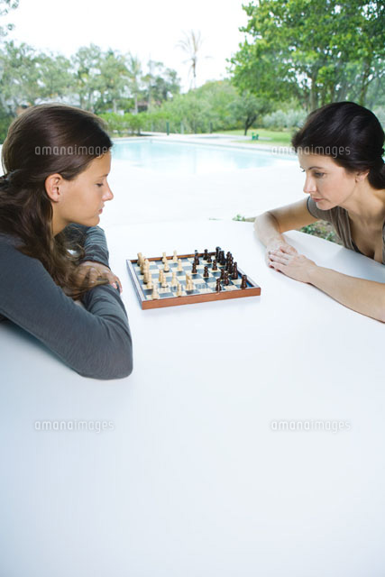 Mother & daughter playing chess together