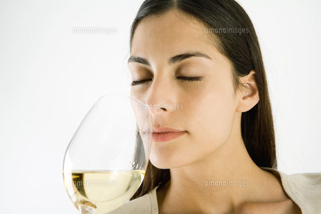 Woman smelling glass of white wine