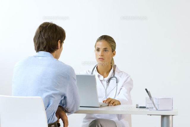 Female doctor sitting across from male patient at desk