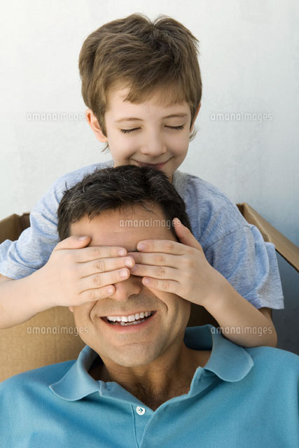 Boy with hands over his father's eyes,