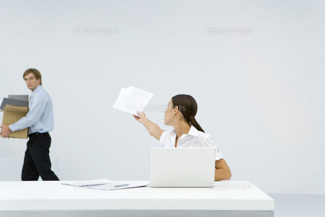 Woman sitting at desk, reaching back to hand documents