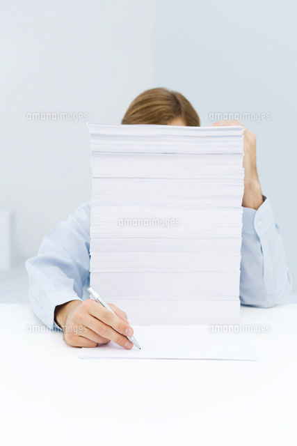 Man hiding behind tall stack of paper