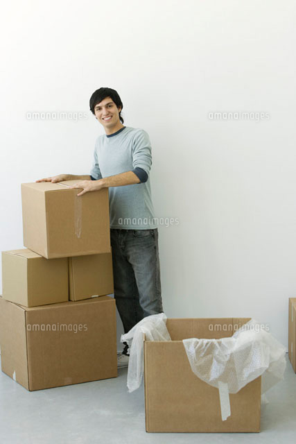 Man standing by stack of cardboard boxes, smiling at camera