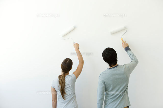 Couple using paint rollers on wall, rear view