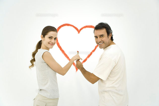 Couple standing in front of heart painted on wall