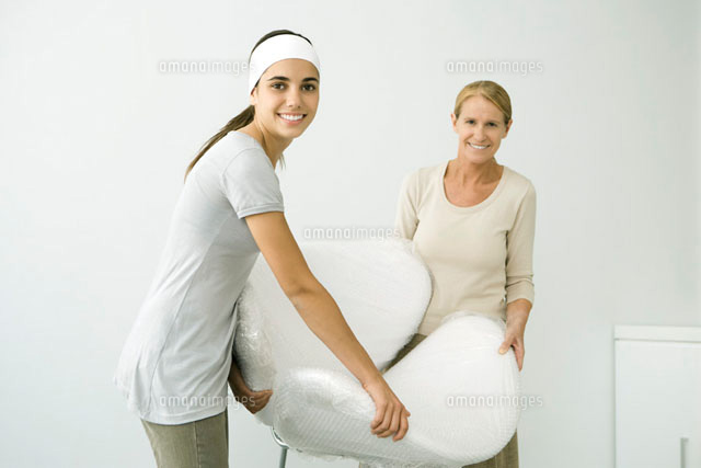 Mother and daughter carrying chair covered in bubble wrap