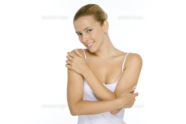 Woman in tank top touching shoulder and arm