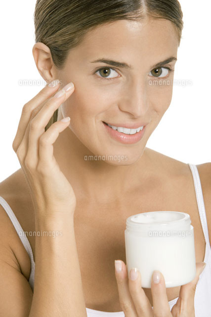 Woman applying moisturizer to face,smiling at camera