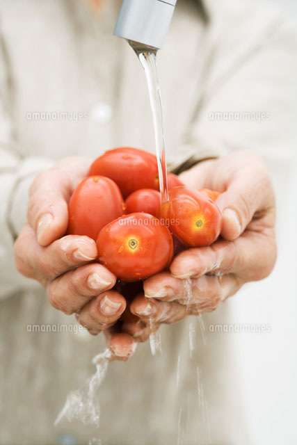 Woman rinsing handful of tomatoes under faucet