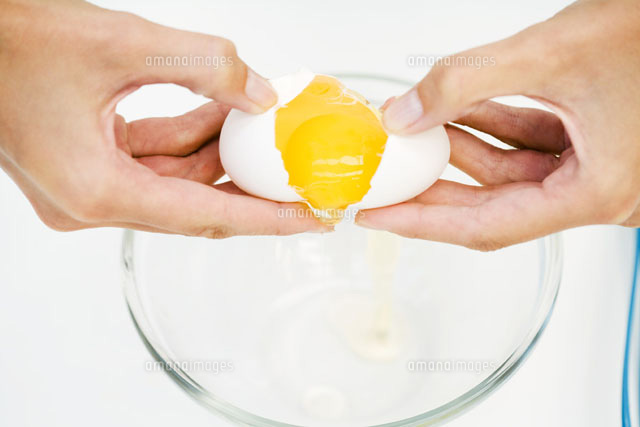 Woman cracking egg into mixing bowl,cropped view of hands