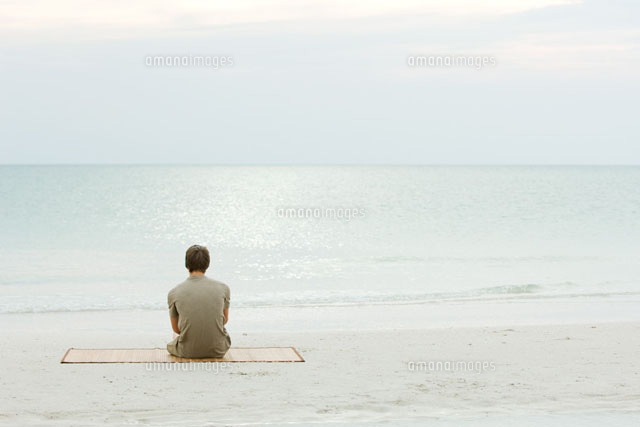 Teenage boy sitting at the beach,looking at the ocean