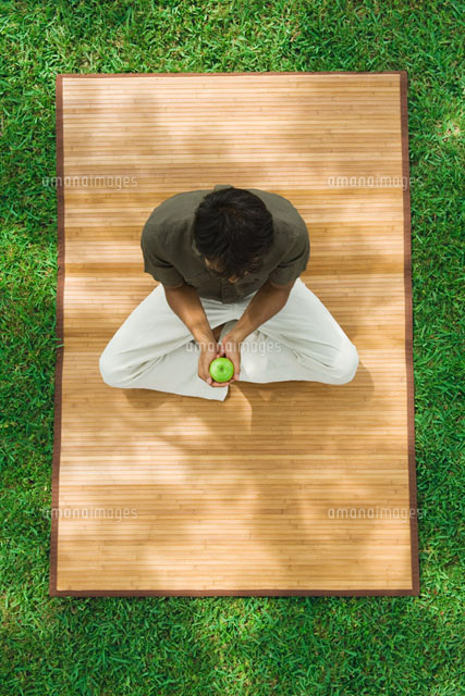 Man sitting indian style on mat outdoors,holding apple