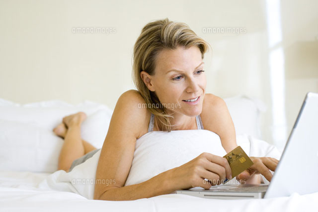 Woman lying on stomach in bed,using laptop and credit card