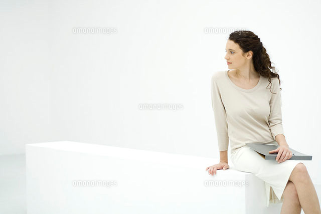 Female professional sitting on ledge,holding binderr