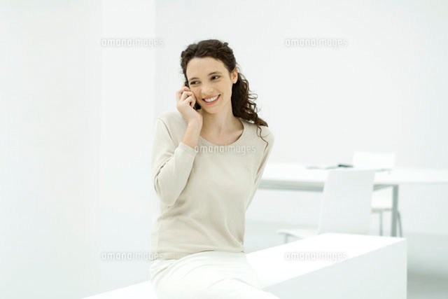 Woman in office,using cell phone,smiling