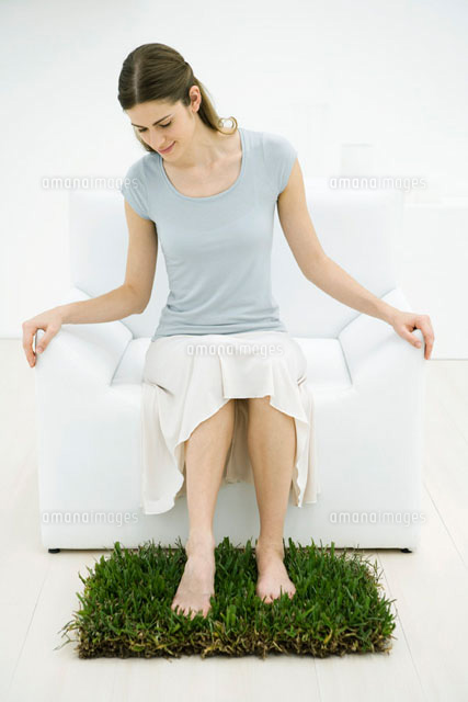Woman sitting in arm chair,feet on patch of grass