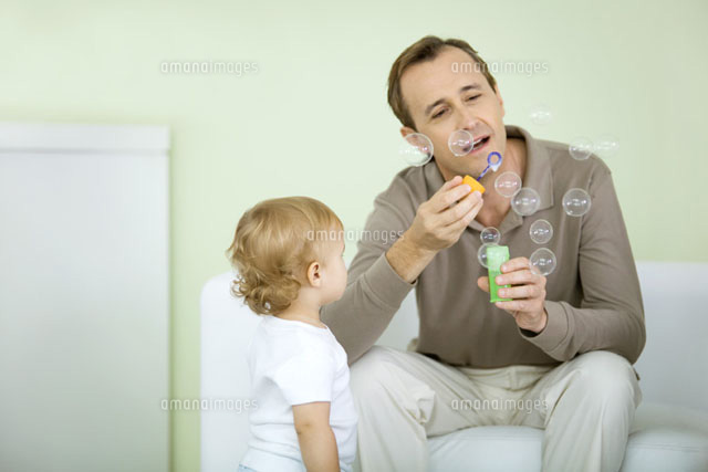 Father and toddler blowing bubbles together