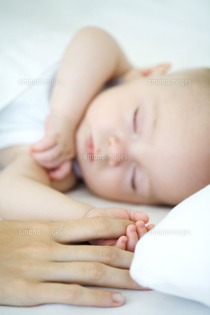 Adult holding sleeping baby's hand,cropped view