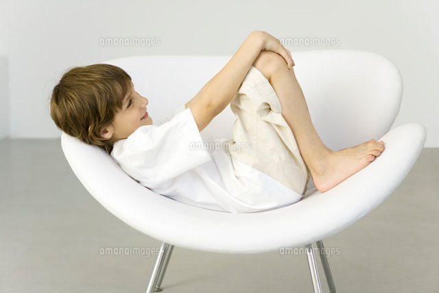 Boy reclining in chair,smiling,side view