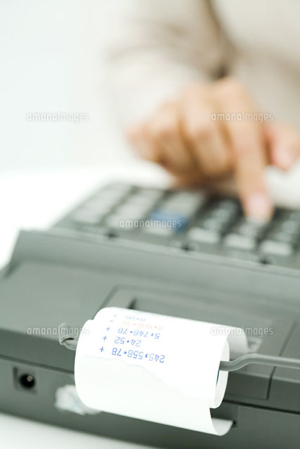 Person using adding machine,cropped view