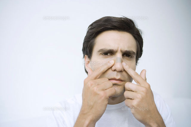 Man applying adhesive bandage on his nose