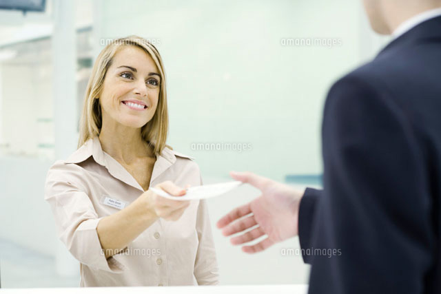 Woman smiling,handing document to businessman