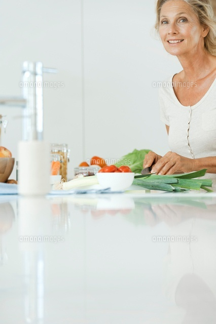Mature woman preparing healthy meal, smiling at camera