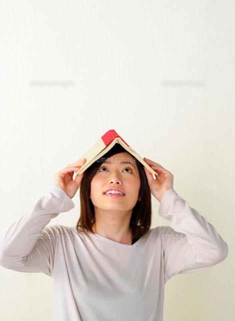 本を頭に置いて上を見る女性11004019613の写真素材イラスト素材