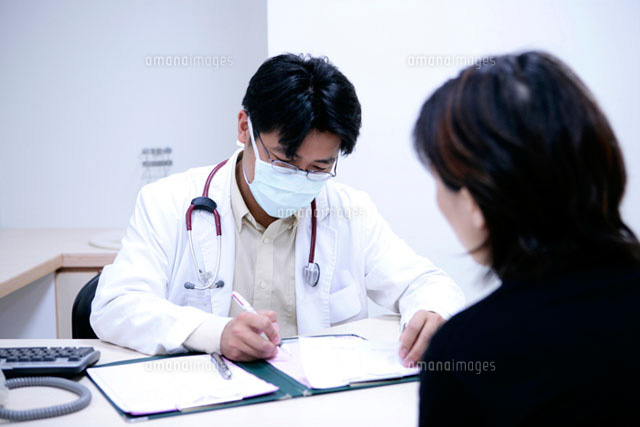 doctor writing on clipboard by patient