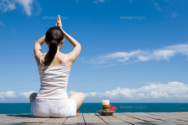 Young woman sitting by beach