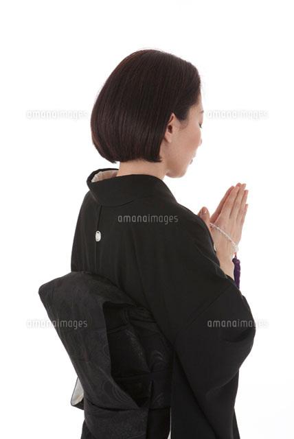 数珠を持って手を合わせる喪服姿の女性 後ろ斜め11014030517の写真素材