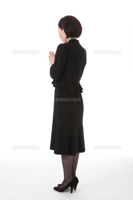 手を合わせ目を閉じる喪服姿の女性 斜め後ろ11014030648の写真素材
