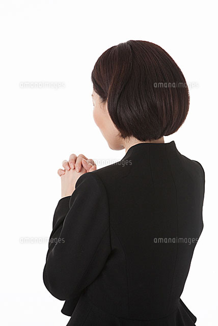 手を組み目を閉じる喪服姿の女性 斜め後ろ11014030656の写真素材