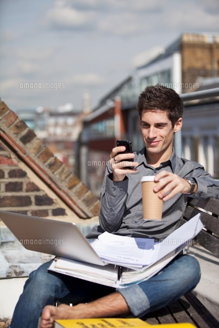 Young man sitting in a roof garden with laptop and mobile ph