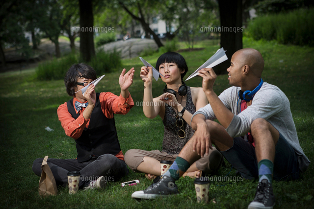 Three friends holding paper planes in park