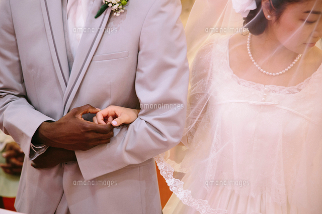 Cropped view of bride wearing veil and bridegroom holding hands