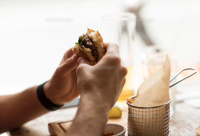 Hand of young man eating burger in restaurant