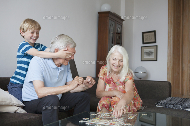 Boy covering grandfather's eyes while senior woman arranging jigsaw puzzle at table in living room