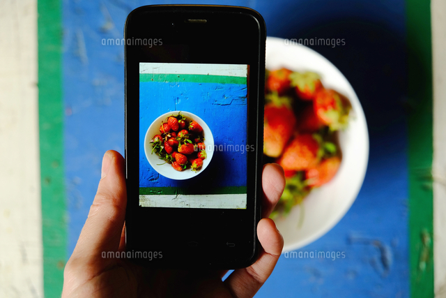 Hand of Caucasian woman photographing bowl of strawberries