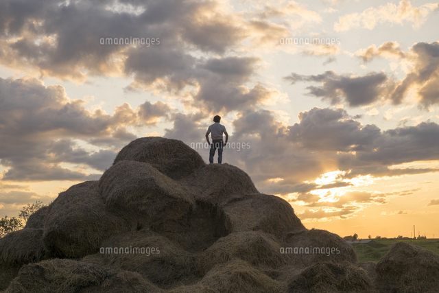 Caucasian man standing on rock pile at sunset