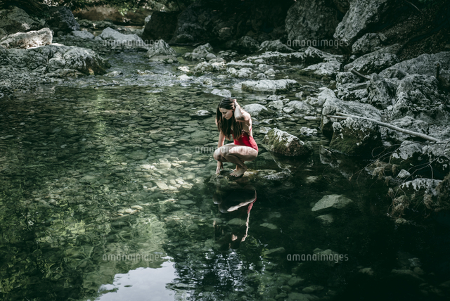 Caucasian woman crouching on rocks at pool of water