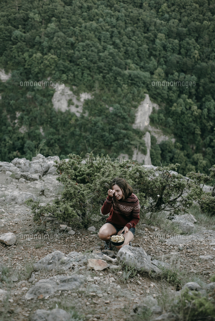 Smiling Caucasian woman crouching on mountain holding pan
