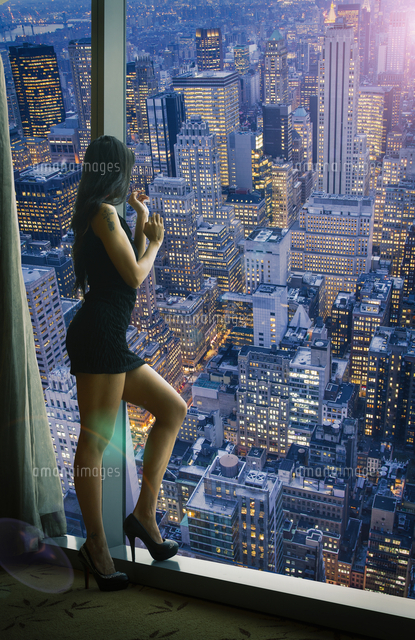 Chinese woman admiring cityscape at night from window