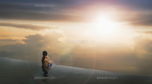 Chinese woman in infinity pool admiring sunset