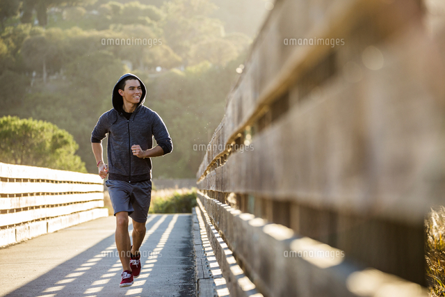 Smiling Mixed Race man running on footbridge